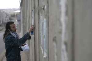 Palestinian graffiti artist Njm sprays graffiti message on controversial Israeli barrier in al-Ram